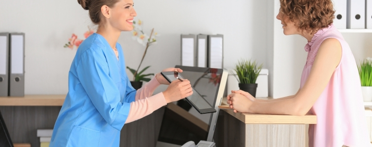 Photograph of a receptionist checking in a patient