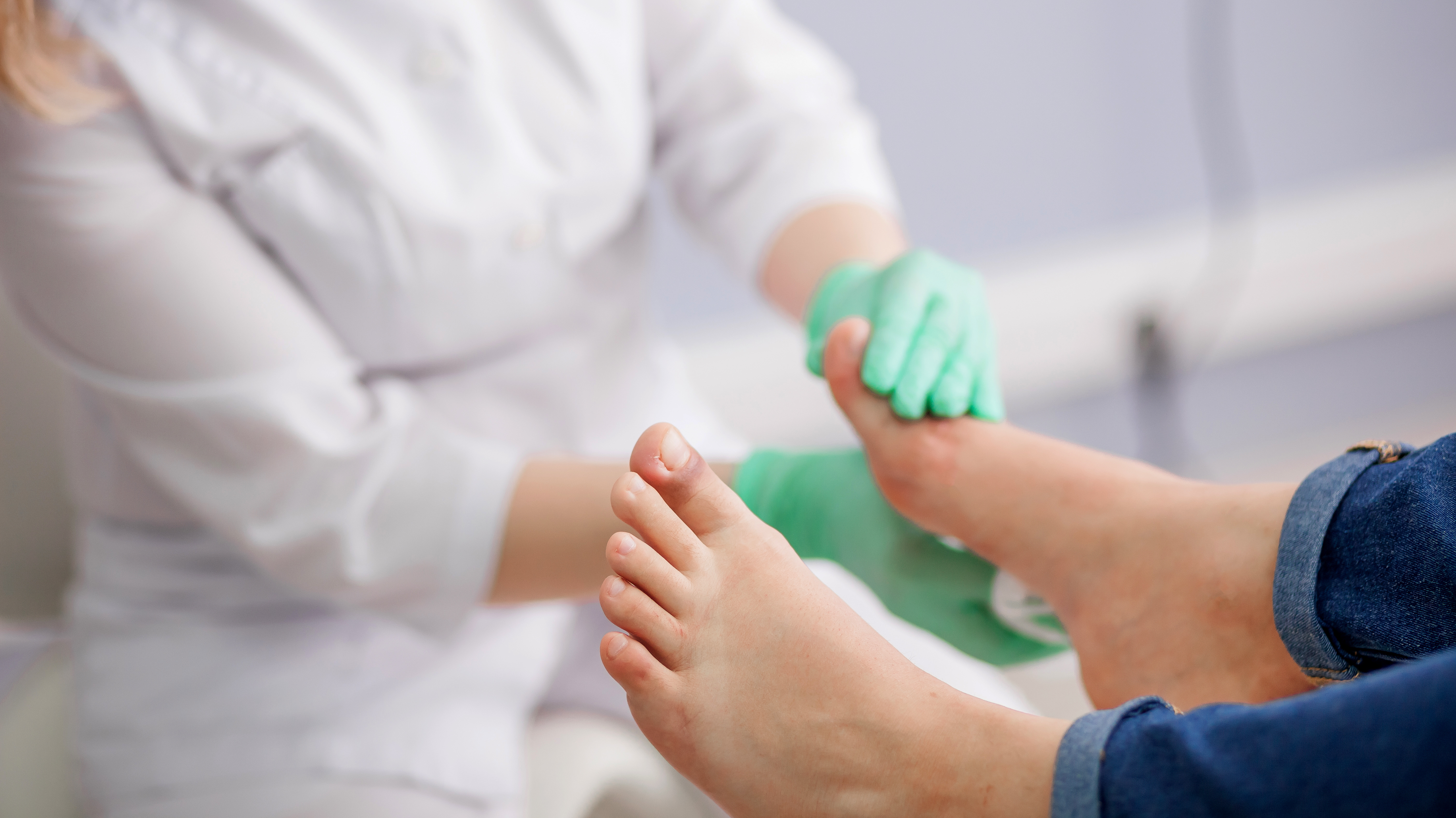 Photograph of podiatrist examining feet with injured great toe