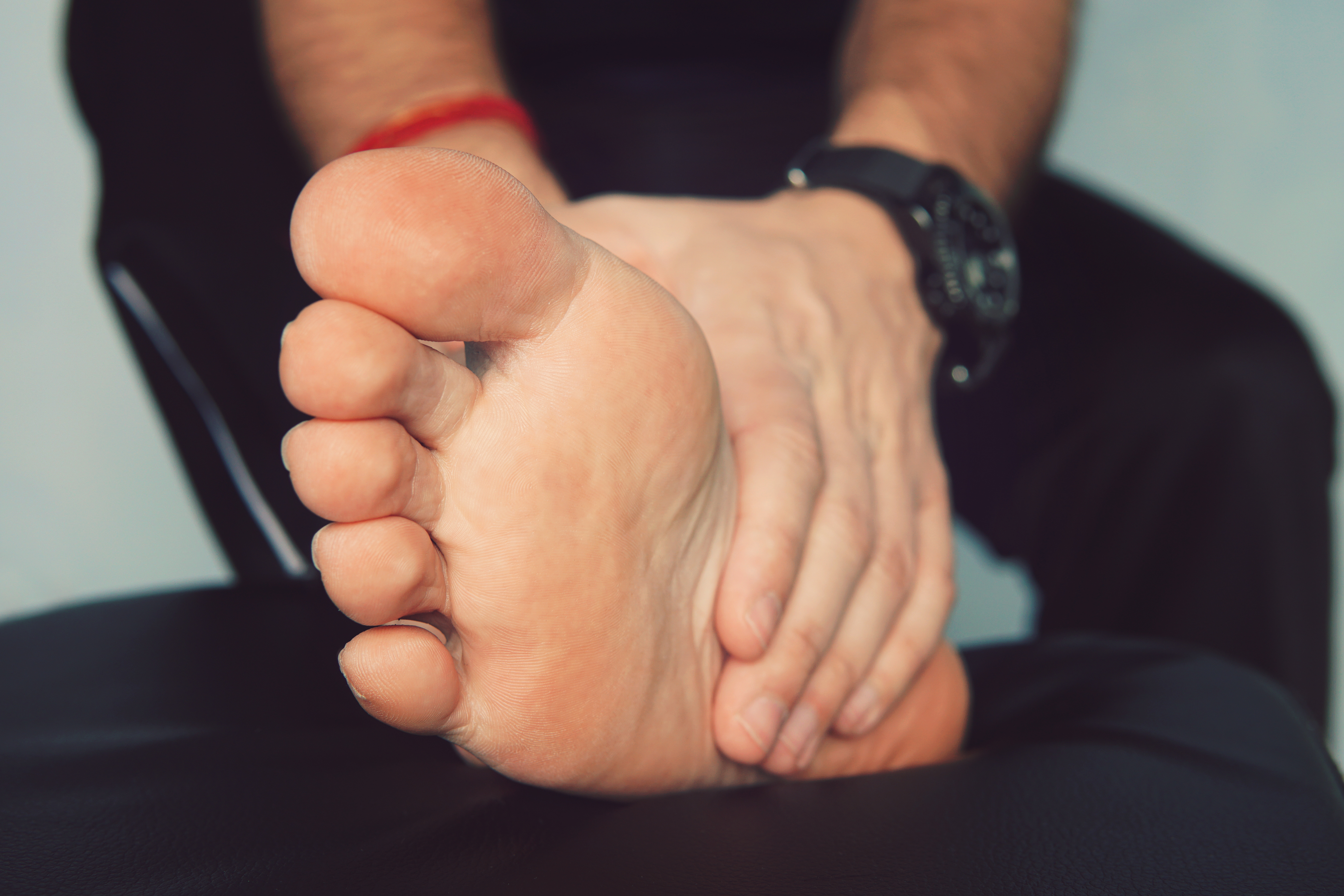 Man's hand massaging a foot. Man with painful and inflamed gout on his foot around the big toe area.