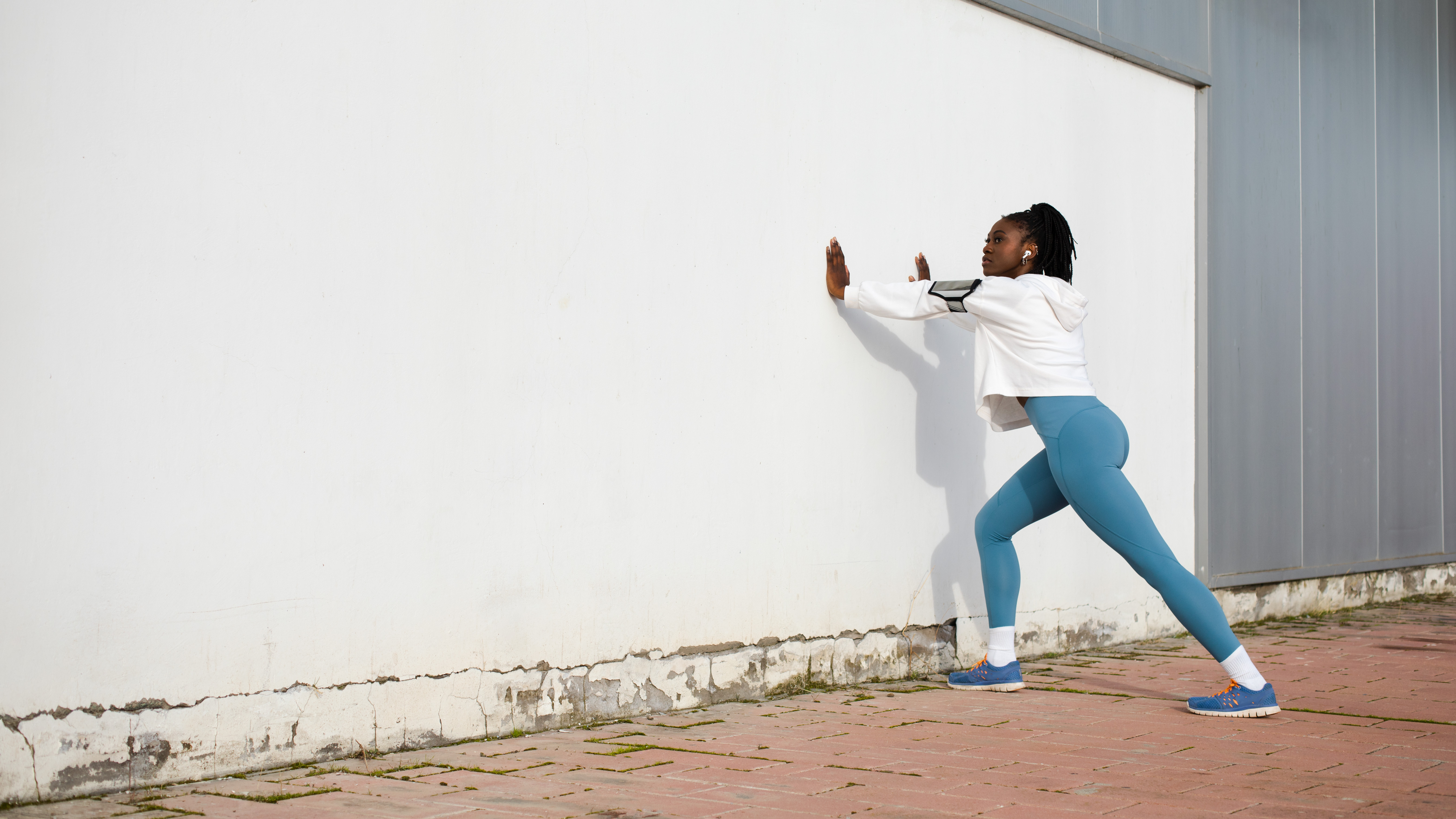 Photograph of female athlete training outside; stretching her calf muscles before a run.